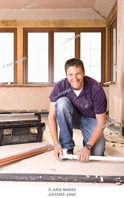 Smiling man kneeling next to toolbox and pipes