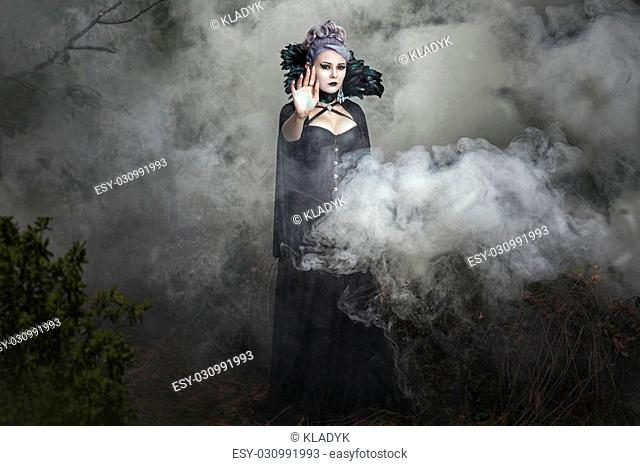 Gothic girl in black clothes stands in the smoke