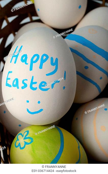 Close up, overhead shot of multiple creamy white ceramic eggs in a wicker biscuit, decorated with patterns, a smiling face and the words 'Happy Easter' on...