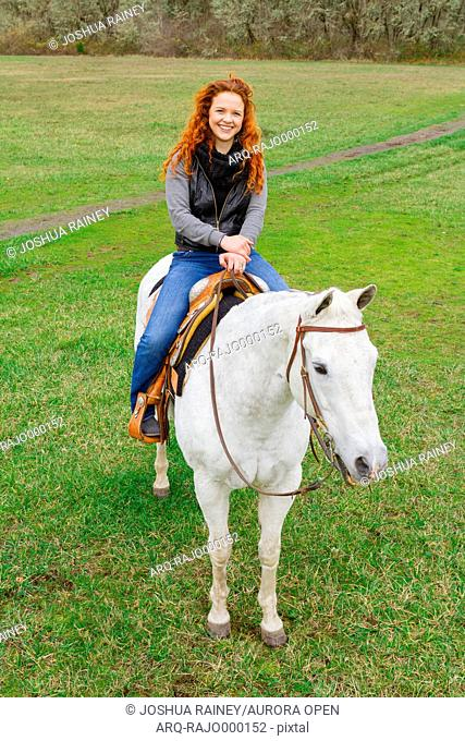 Portrait of an equestrian girl with red hair and a white horse at a horse riding public property