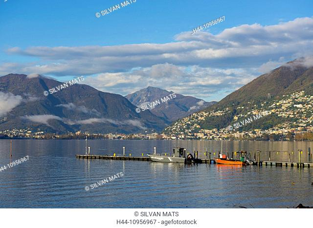 Alpine lake maggiore with a pier and mountains and blue sky with clouds in locarno ticino Switzerland, Europe