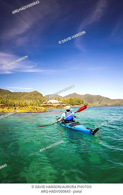 A woman kayaks through a remote flatwater landscape with mountains in the background