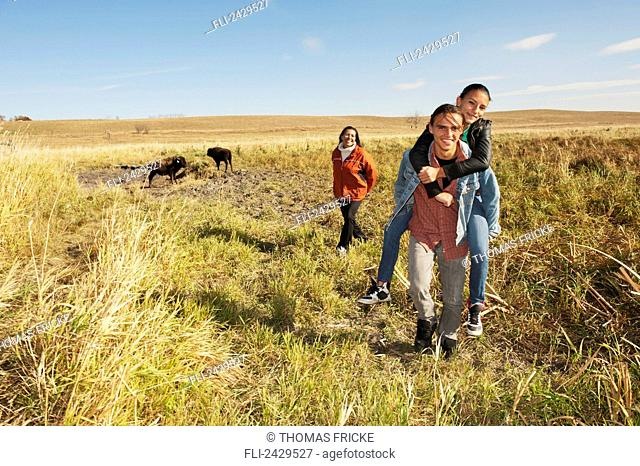 Native American family walking through a buffalo ranch; Rossburn, Manitoba, Canada