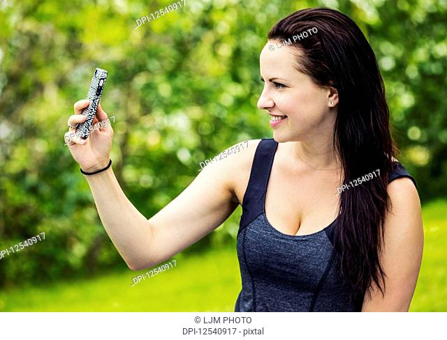 Beautiful young woman taking a self-portrait while enjoying the outdoors in a park; Edmonton, Alberta, Canada