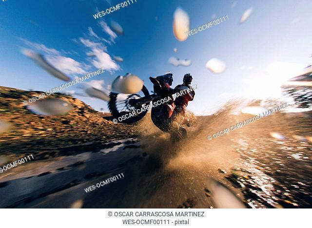 Motocross driver driving through the water, splashing
