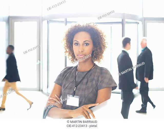 Portrait of young businesswoman with crossed arms standing in office