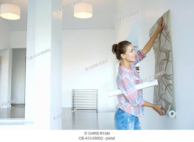Woman hanging wallpaper in new house