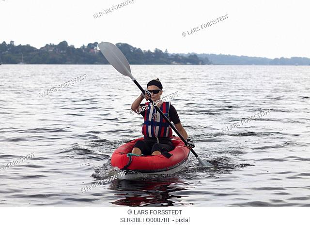 Woman kayaking on still lake