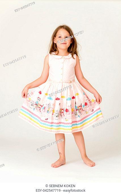 Happy little cute girl showing a ballerina dance figure