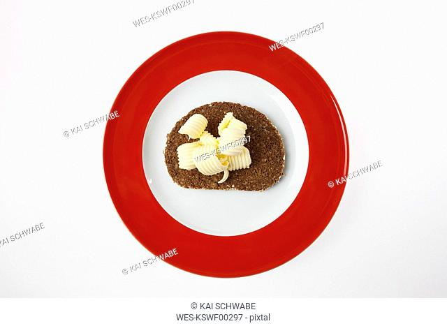 Slice of bread with butter on plate, elevated view