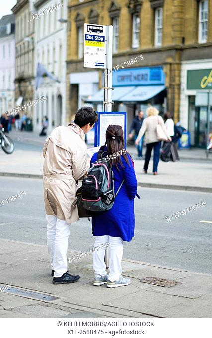 A couple of chinese tourists at a bus stop checking public transport bus times and services in Cirencester, Gloucestershire, England UK