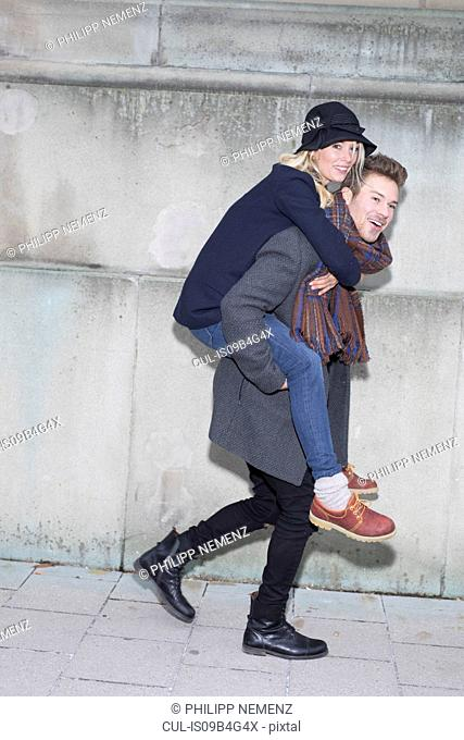 Stylish man giving girlfriend piggyback on city sidewalk