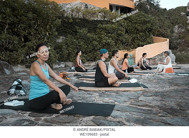 Yoga retreat, group of people sitting and meditating on mats, Puerto Vallarta - Mismaloya, Mexico