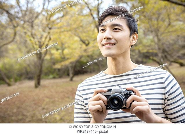 Portrait of young smiling man with a camera in forest