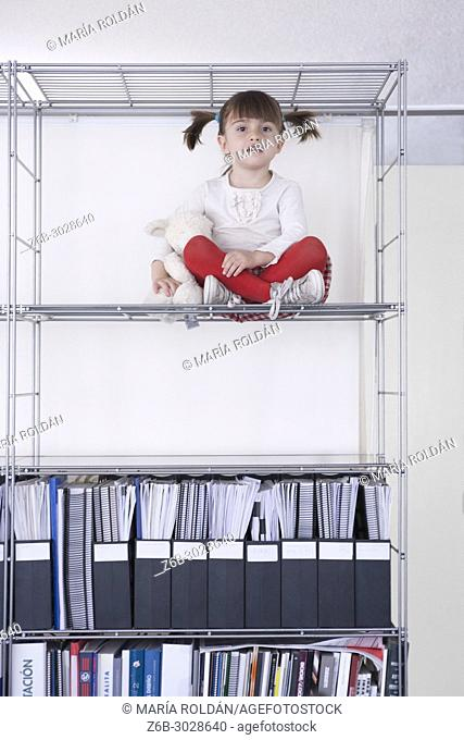 little girl seated high up in a bookshelf