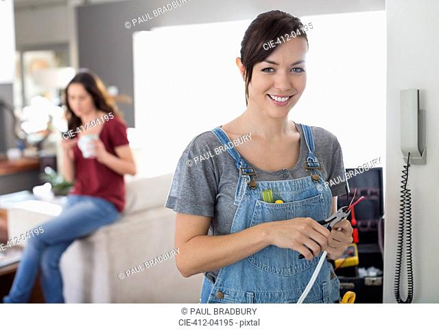 Female electrician working on telephone in home