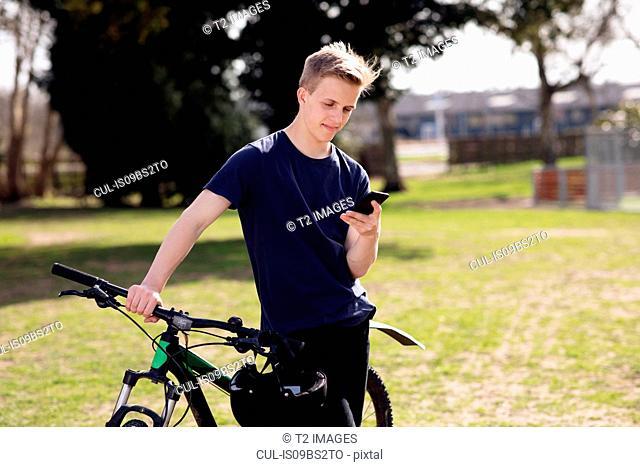 Teenage boy texting on pushbike
