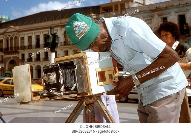 Photographer using ancient handmade camera to photograph people on the steps of the Capitolio, Havana, Cuba, He uses paper for the negative and rephotographs it...