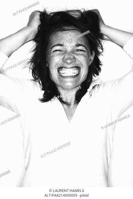 Woman gritting teeth, pulling hair, portrait, b&w