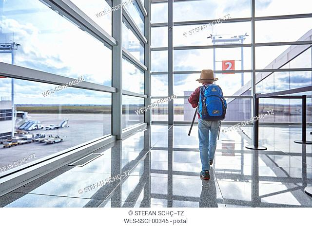Boy with backpack at the airport running towards departure gate