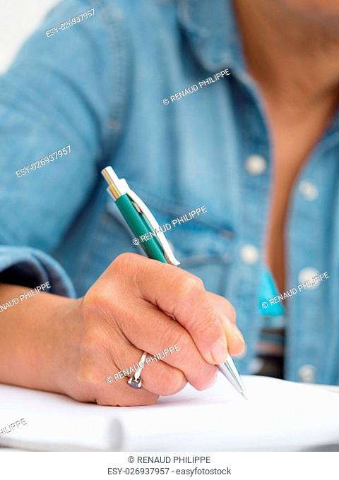a hand of adult woman writing with pen
