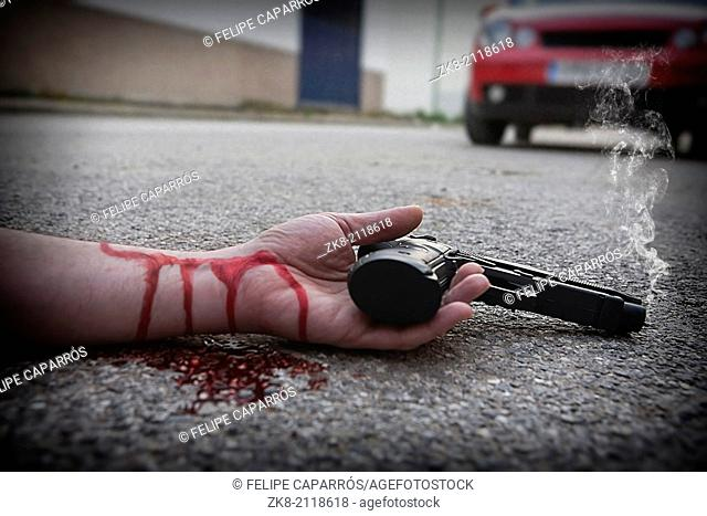 Man with gun in hand bloodstained lies dead in the asphalt murder victim