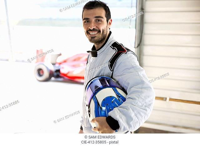 Portrait confident male formula one race car driver holding helmet in repair garage