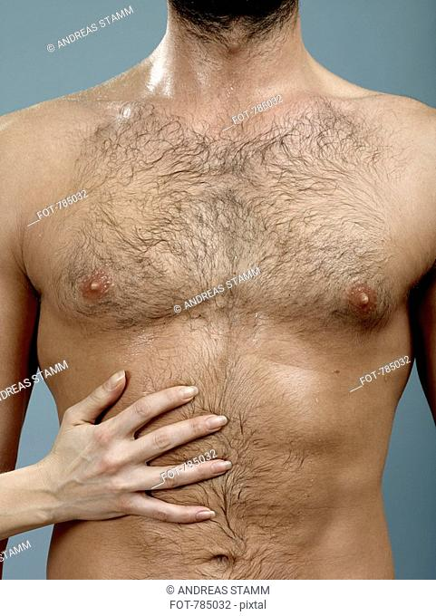 A woman's hand touching a man's abdomen