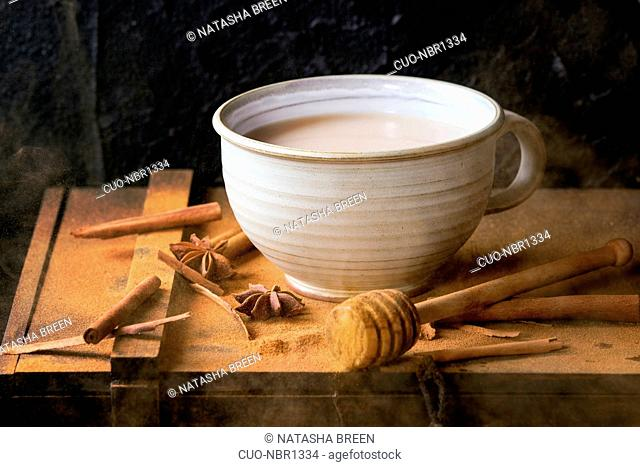 White ceramic cup of hot masala chai, served with honey on honey dipper, anise, cinnamon sticks and powder over black wooden box over black textured background