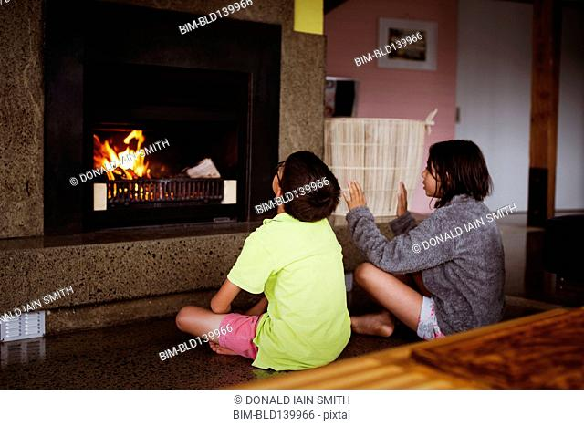 Mixed race children relaxing by fireplace in living room
