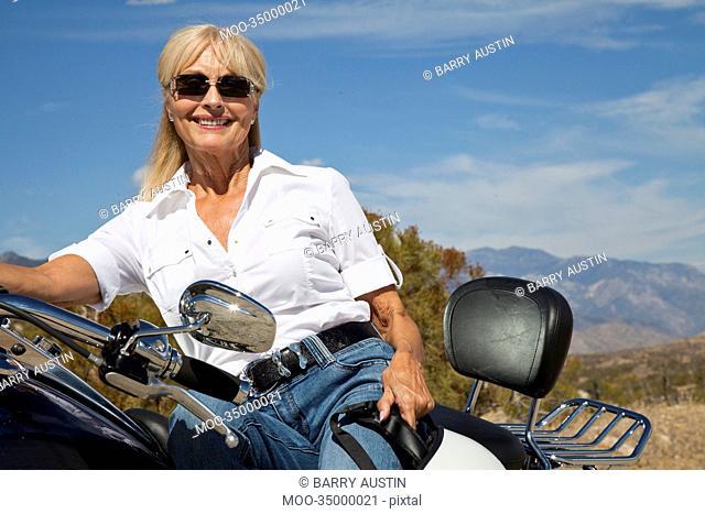 Senior woman sitting on motorcycle on desert road