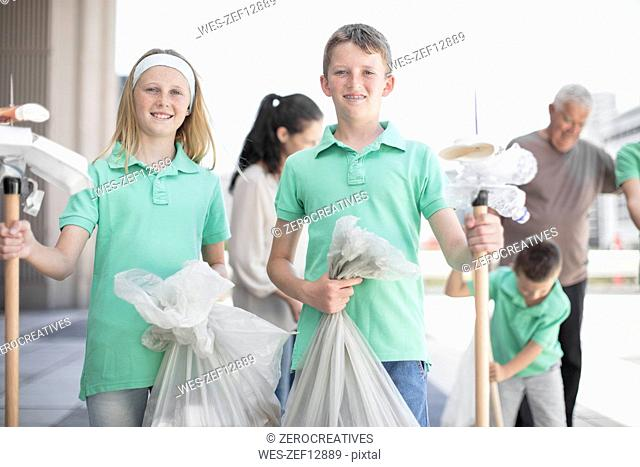 Group of volunteering children collecting garbage with litter sticks