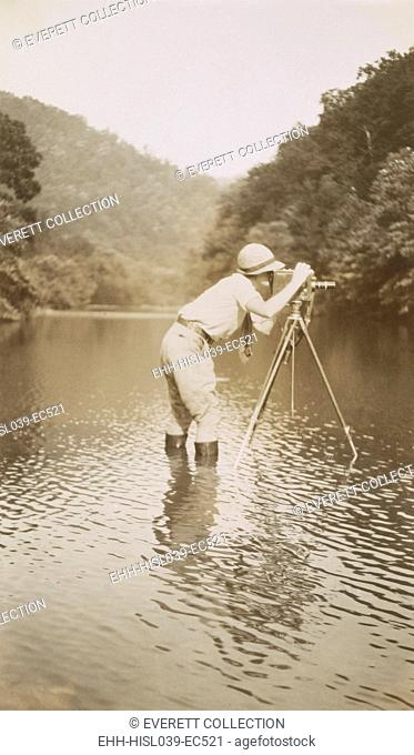 Marvin Breckinridge Patterson taking a photograph while standing in a river, 1935. She was a widely published photographer in the 1930s and used her middle name