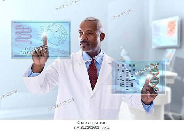 Black doctor looking at digital display in laboratory