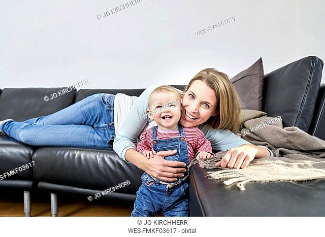 Happy mother and baby girl at home on couch