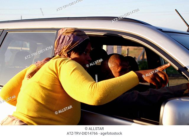 AFRICAN WOMAN POINTS DIRECTION; NEW BRIGHTON TOWNSHIP, PORT ELIZABETH, SOUTH AFRICA; 01/07/2010