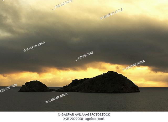 Dark sunset clouds over the islet of Vila Franca do Campo, off the coast of Sao Miguel island. Azores, Portugal