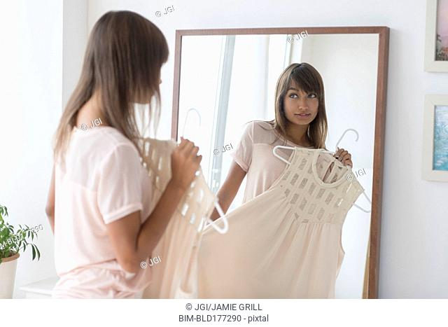 Mixed race woman examining dress in mirror
