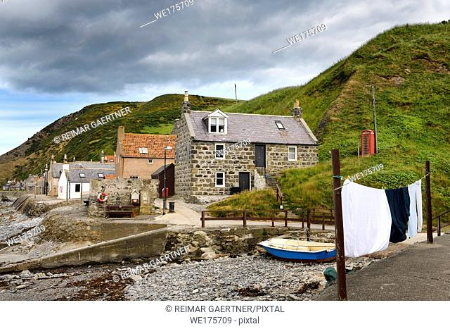 Single row of houses of Crovie coastal fishing village on Gamrie Bay North Sea Aberdeenshire Scotland UK with red telephone box and wash on line