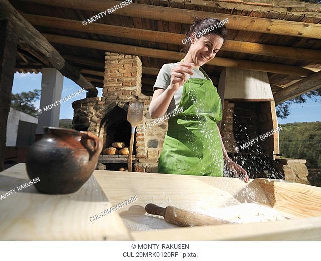 Woman sprinkling salt in bread dough