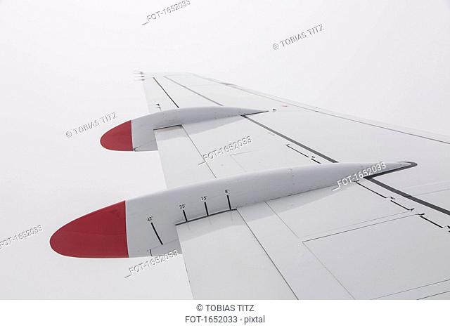 Cropped image of aircraft wing flying against sky
