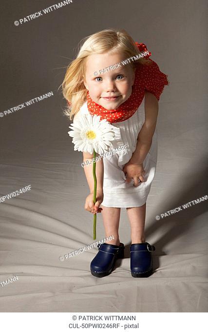 Girl holding flower in studio