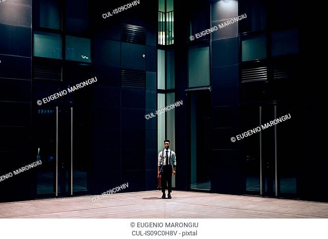 Businessman standing in front of office building, Milano, Lombardia, Italy