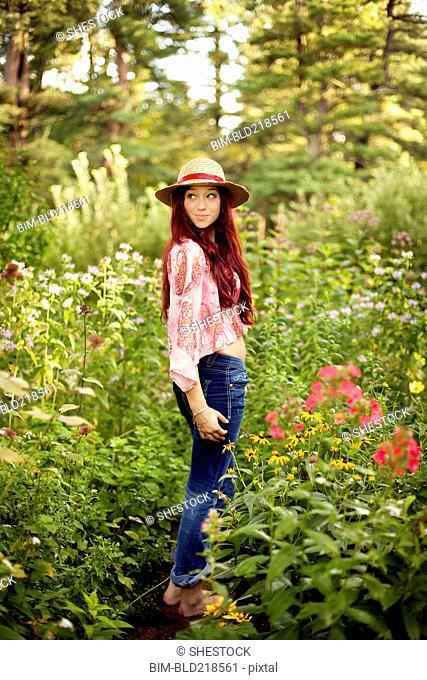 Girl wearing straw hat in garden