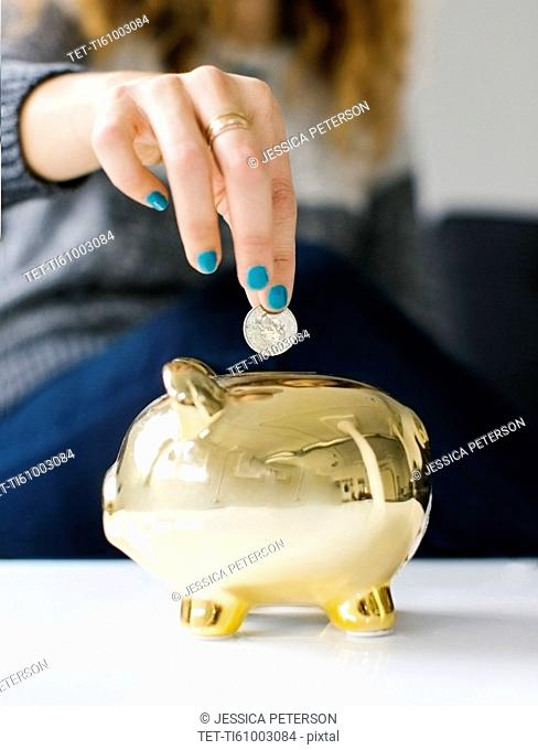 Woman dropping coin into gold piggy bank