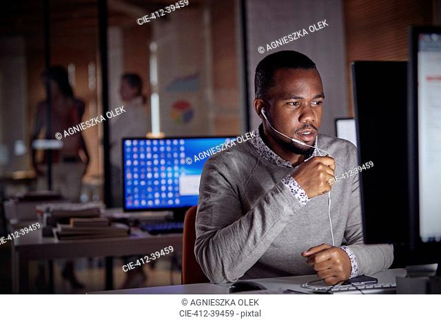 Businessman working late at computer, using hands-free headphones talking on telephone