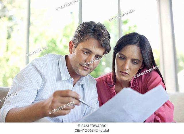 Couple reading papers together on sofa