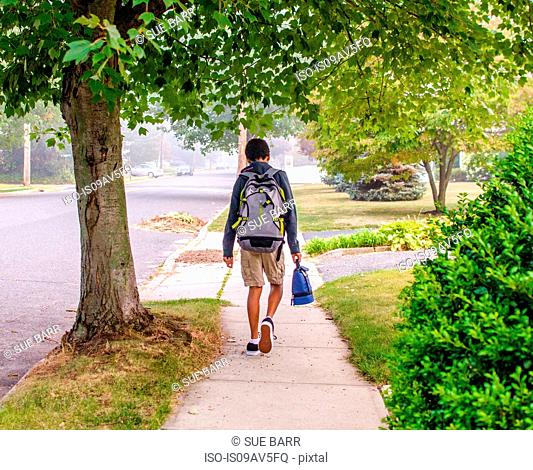 Boy with backpack walking on sidewalk