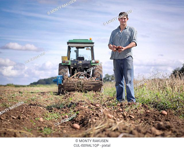 Portrait of farmer with crop of organic potatoes