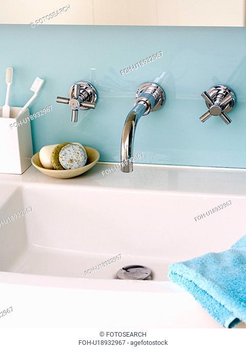 Close-up of chrome taps and glass splashback above modern rectangular basin